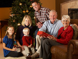 Fototapety Multi Generation Family Opening Christmas Presents In Front Of T