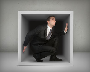 Businessman in a box,gray background