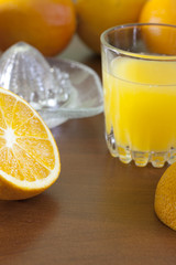 Orange fresh juice with squeezer on table