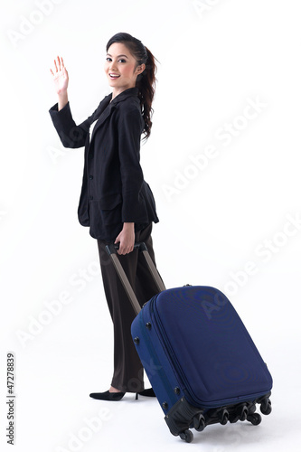 happy woman pulling luggage and waving her hand