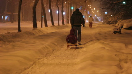 Father Pulling Son On Sledge Along Snowy Street