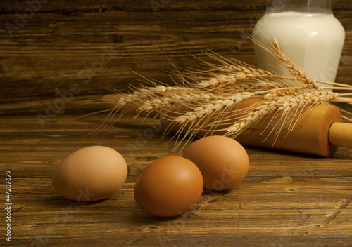 Three eggs , jug with milk and wheat seeds on the wooden table.