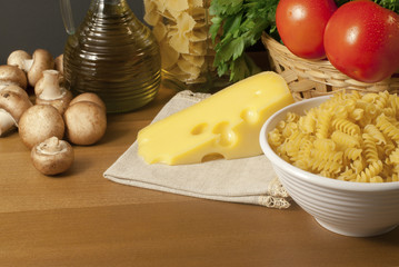 Composition of pasta, tomatoes, cheese, olive oil and mushrooms.