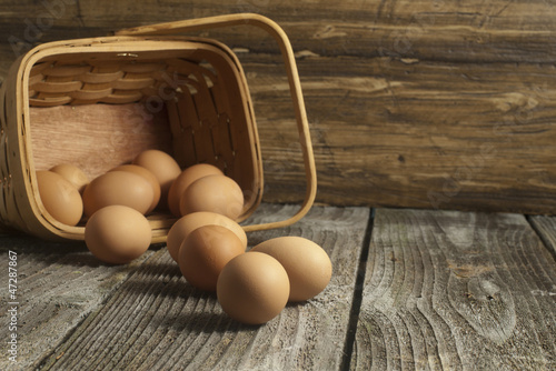Basket with organic eggs on a weathered wooden table.