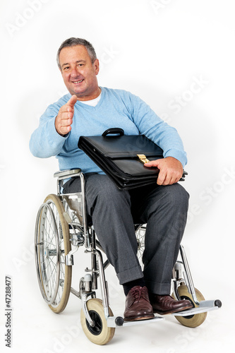 Friendly man in wheelchair holding thumbs up