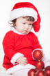 Christmas toddler in Santa hat playing with balls