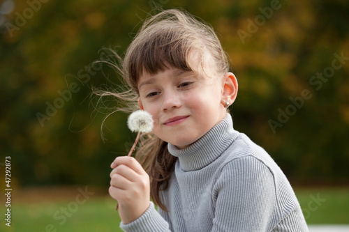 little girl enjoys fluffy dandelion