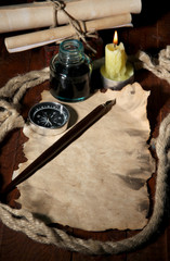 Old paper with ink pen near lighting candle on wooden table