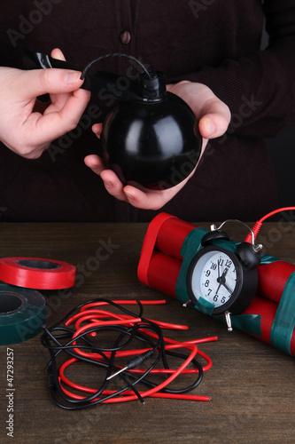 Human makes timebomb on wooden table on black background