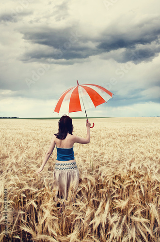 Girl with umbrella at field.