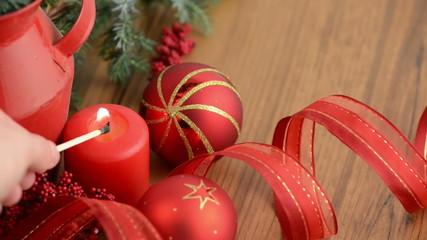 Kerze wird angezündet mit Weihnachtsbaumkugeln und Tannengrün