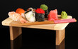delicious sushi served on wooden board isolated on black