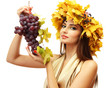 beautiful young woman with yellow autumn wreath and grapes,