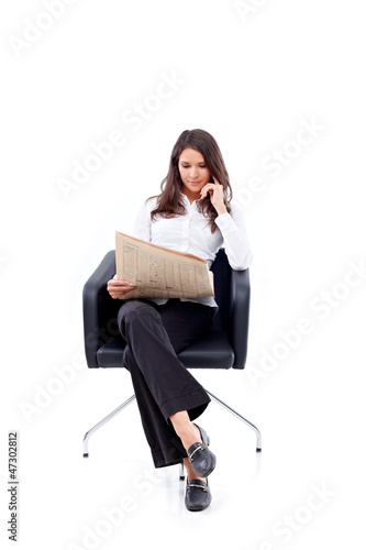 Casual 20s woman reading stock rates in newspaper