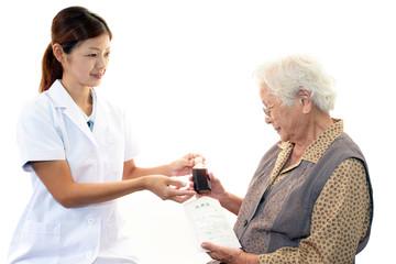 薬の説明をする薬剤師と高齢者