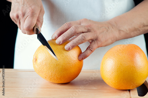 Female hands cutting a grapefruit, horizontal shot