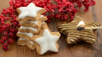 Weihnachtsgebäck wie Zimtsterne und brennende Kerze