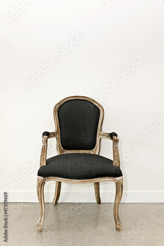 Antique armchair near wall