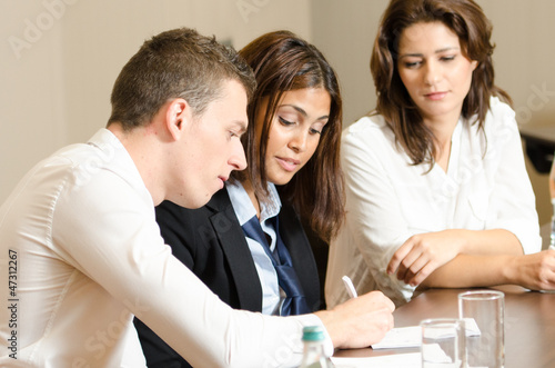 Business persons talking and writing