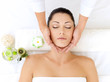 Woman having massage of head in spa salon