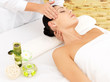 Woman having massage of face in spa salon
