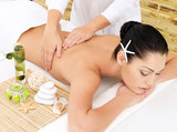 Woman on therapy massage of back in spa salon
