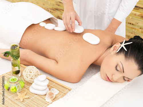 Woman having hot stone massage of back in spa salon
