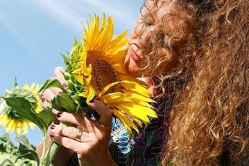 portrait woman sniffs sunflower