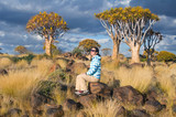 Quiver tree forest african landscape, woman tourist in Namibia