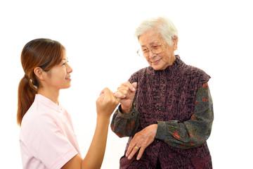 指きりをする高齢者と看護師