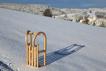 Holzschlitten im Schnee