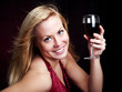 woman holding red wine over dark
