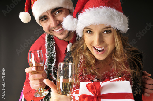Funny Christmas couple with glasses of champagne  covering dark