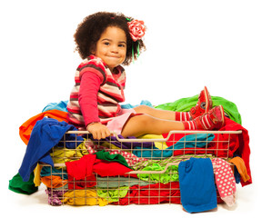 Black girl sitting in the basket with clothes