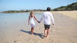 couple holding by hands and walking along coastline