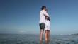 Happy man embracing his girlfriend and standing in ocean
