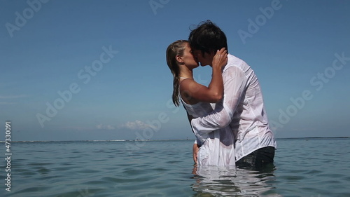 Passionate couple kissing and hugging each other in ocean