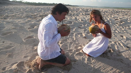 Happy couple drinking coconuts then going away