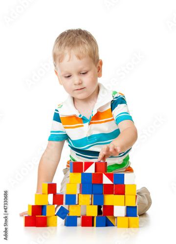 Child boy playing toy blocks isolated on white