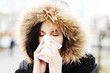 Woman sneezes during cold day and holds a tissue.