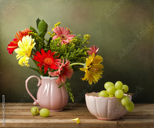 Fotobehang Gerbera Still life with beautiful flower bouquet and green grapes