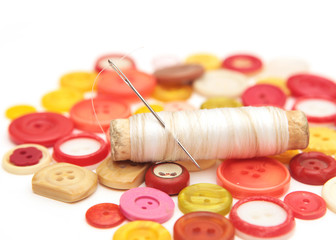 spool of thread with a needle on top of buttons