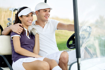 Smiling couple in golf cart