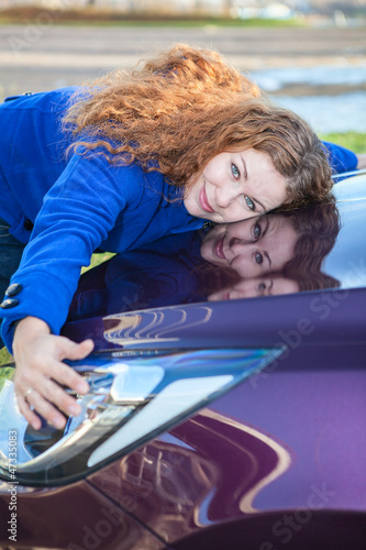 Young female driver hugging hood of new car