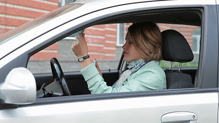 Female making up on driver`s seat of vehicle