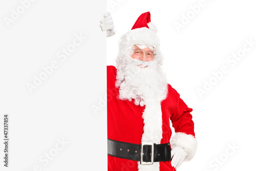 A smiling Santa Claus posing next to a billboard