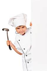 child chef in white uniform and hat hiding behind empty board