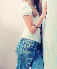 Blonde girl standing near wall