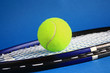 Tennis racket and ball on a blue background.