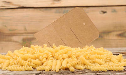pile fusilli pasta with blank tag on wood background